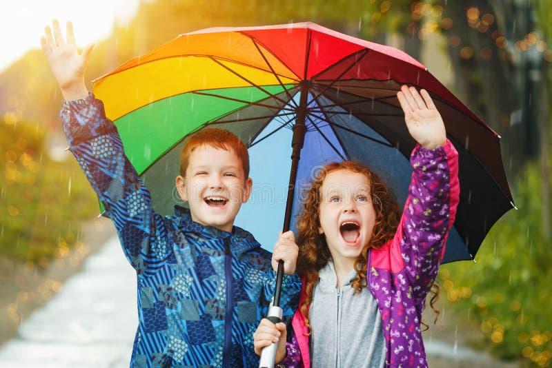 De kinderen onder paraplu genieten van in openlucht aan de herfstregen stock afbeeldingen