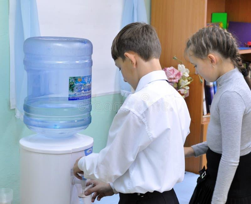 De kinderen op een schoolonderbreking drinken water van de koeler stock foto