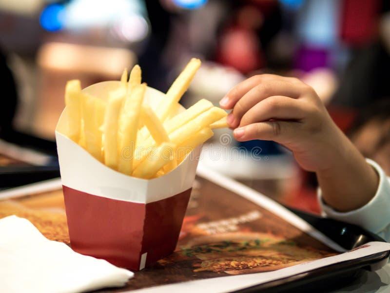 De kinderen overhandigt het Plukken frieten op lijst, Frieten royalty-vrije stock fotografie