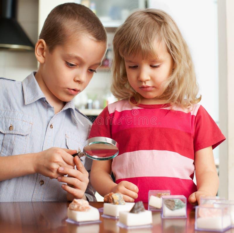 De kinderen overwegen een vergrootglasstenen stock afbeeldingen