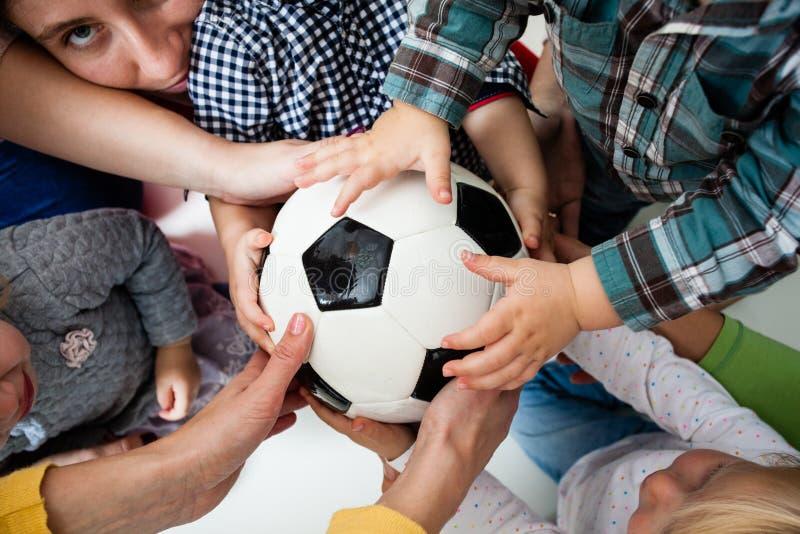 De kinderen rekken zich aan de bal uit stock afbeelding