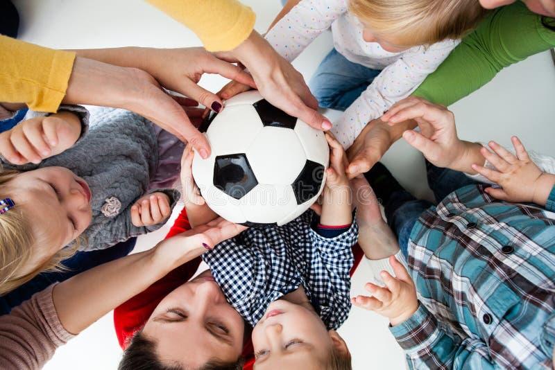 De kinderen rekken zich aan de bal uit royalty-vrije stock afbeelding