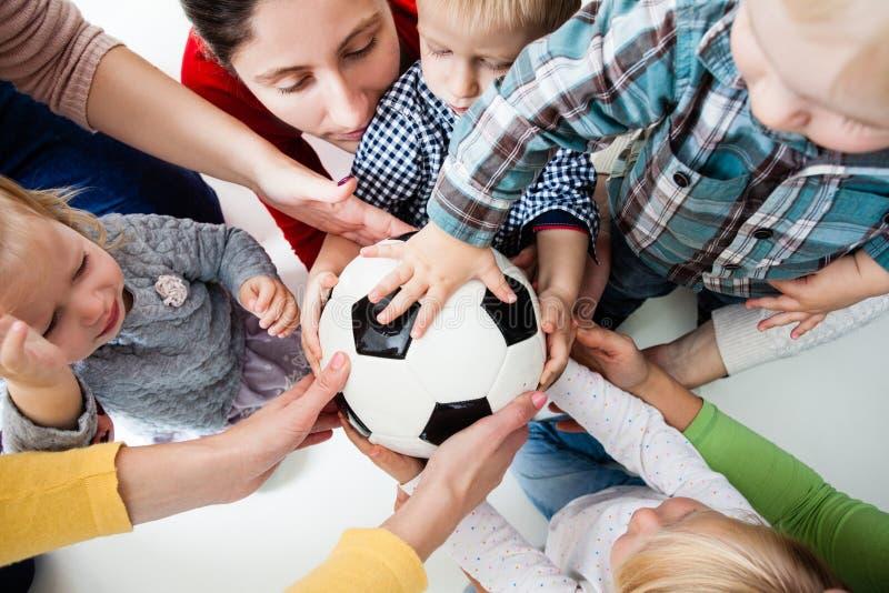 De kinderen rekken zich aan de bal uit royalty-vrije stock afbeeldingen