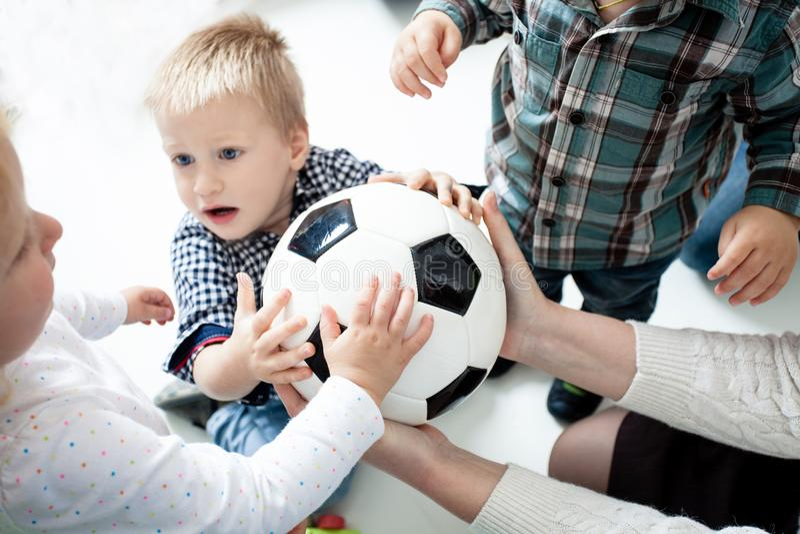 De kinderen rekken zich aan de bal uit stock foto's