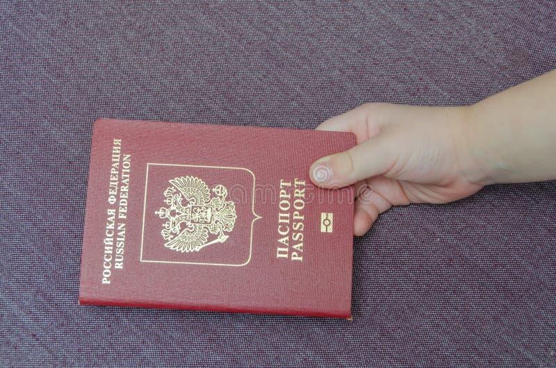De kinderen` s hand gaat het paspoort met het geïnvesteerde geld over royalty-vrije stock afbeeldingen