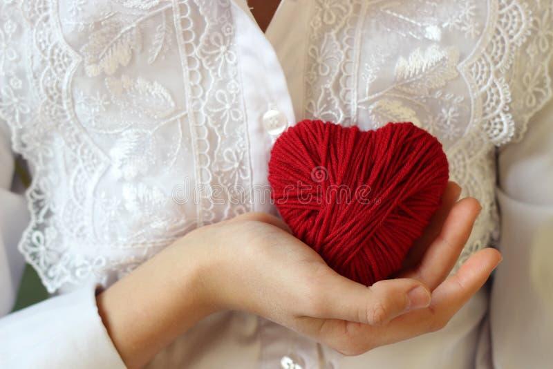 De kinderen` s handen houden een hart van rode draad voor het breien royalty-vrije stock foto's