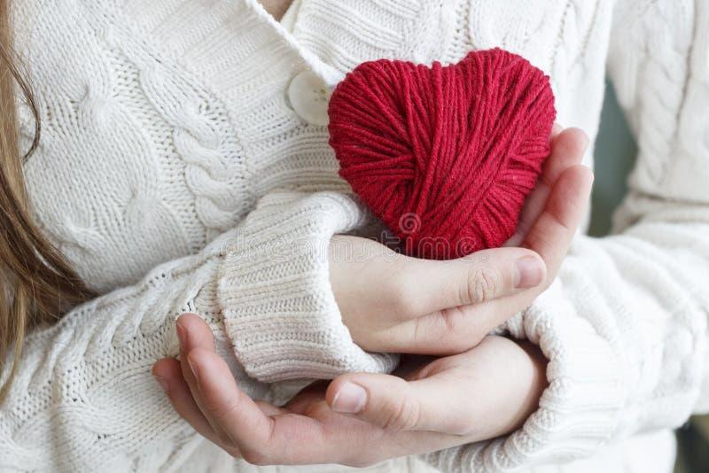 De kinderen` s handen houden een hart van rode draad voor het breien stock fotografie