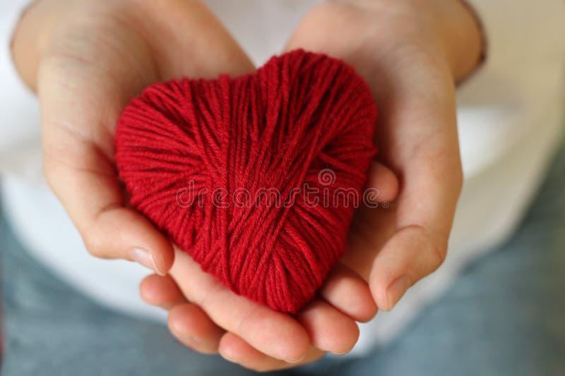 De kinderen` s handen houden een hart van rode draad voor het breien Valent stock afbeelding