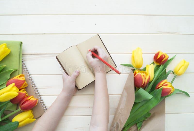 De kinderen` s handen schrijven in een notitieboekje Een brief aan mijn moeder van het kind royalty-vrije stock foto's