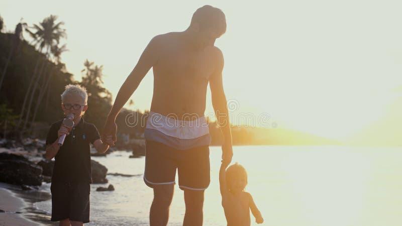 De kinderen` s handen van de papaholding bij mooie zonsondergang en het lopen op tropisch strand Het concept van de reisvakantie stock afbeeldingen