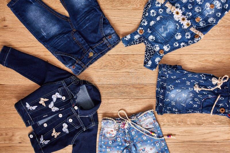 De kinderen` s jeans, het jasje, de denimborrels en het denim kleden zich op houten achtergrond stock afbeeldingen