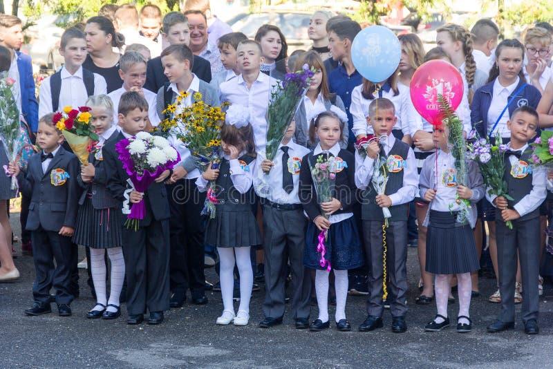 De kinderen schreven in de eerste rang in op school met leraren en ouders bij de inauguratie van het schooljaar in de dag van kno royalty-vrije stock foto's