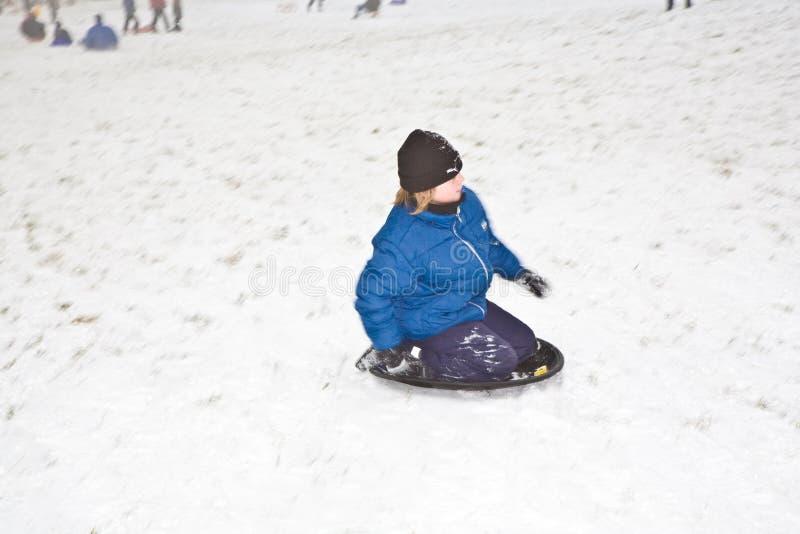 De kinderen sledding onderaan de heuvel in sneeuw royalty-vrije stock foto's