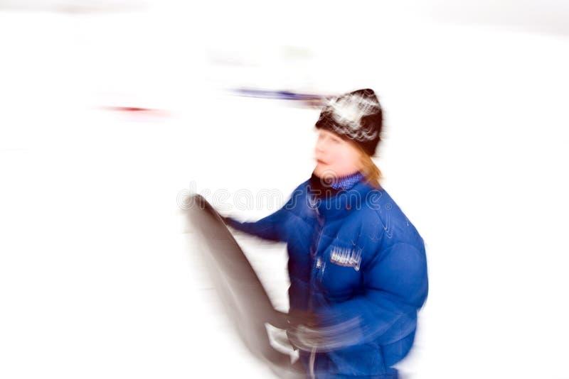 De kinderen sledding onderaan de heuvel in sneeuw royalty-vrije stock fotografie