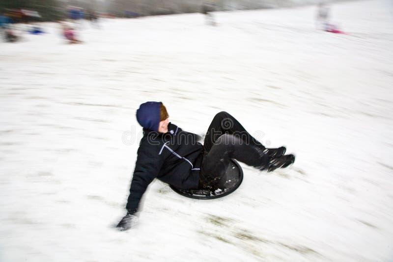 De kinderen sledding onderaan de heuvel in sneeuw stock fotografie