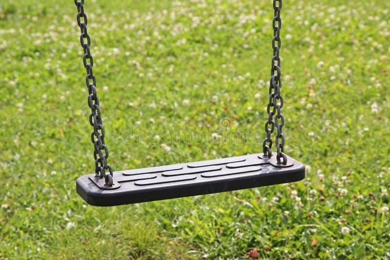 De kinderen slingeren, tegen groen gras, de speelplaats van kinderen stock afbeelding