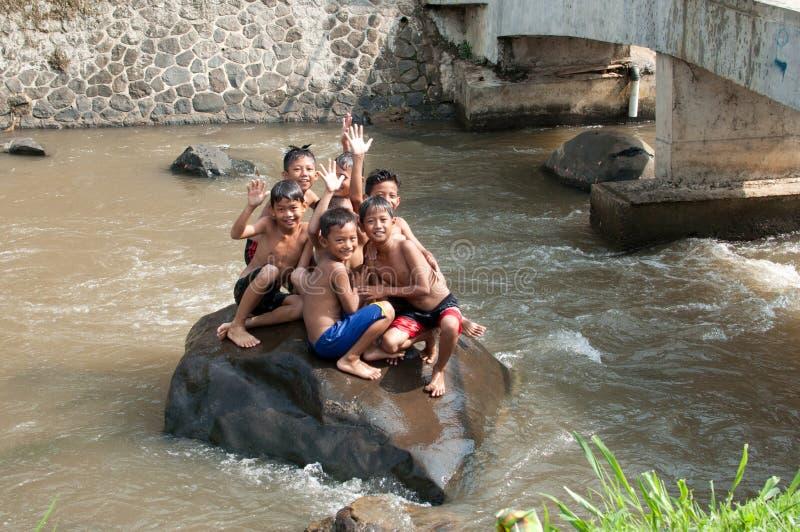 De kinderen spelen bij de rivier stock afbeelding