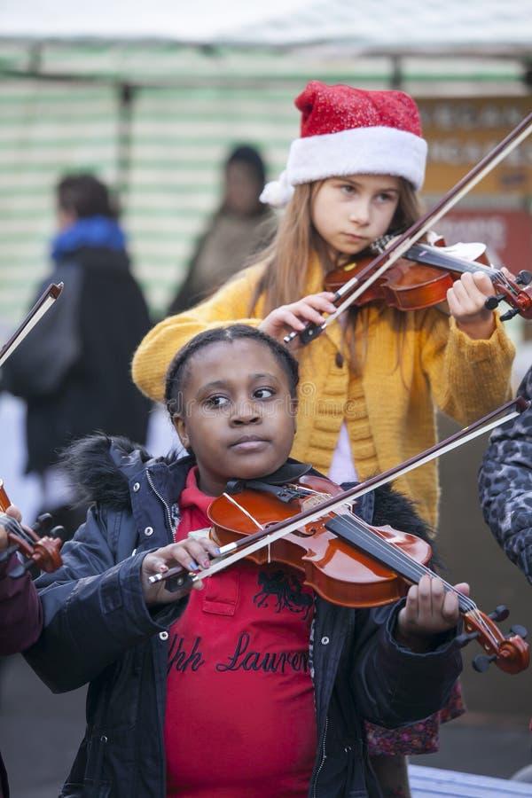 De kinderen spelen de viool bij de Kerstmismarkt royalty-vrije stock foto's