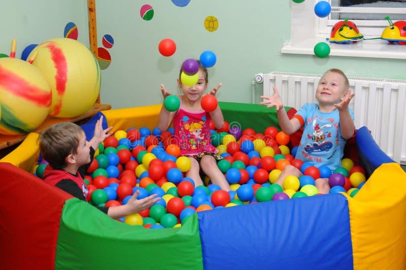 De kinderen spelen in de droge ` pool van ` stock foto