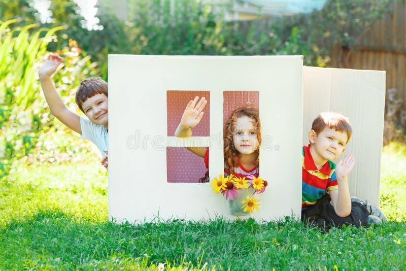 De kinderen spelen in het huis van kartondoos die wordt gemaakt stock afbeelding