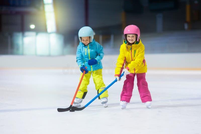 De kinderen spelen ijshockey De sport van de jonge geitjeswinter royalty-vrije stock afbeelding