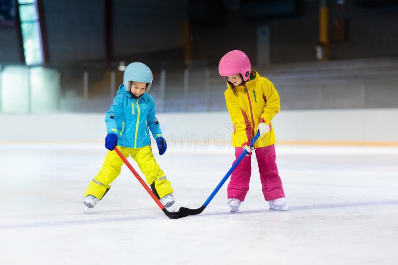 De kinderen spelen ijshockey De sport van de jonge geitjeswinter stock fotografie