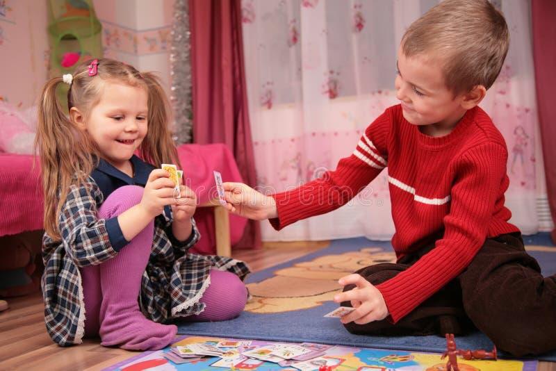 De kinderen spelen kaarten in speelkamer royalty-vrije stock foto's