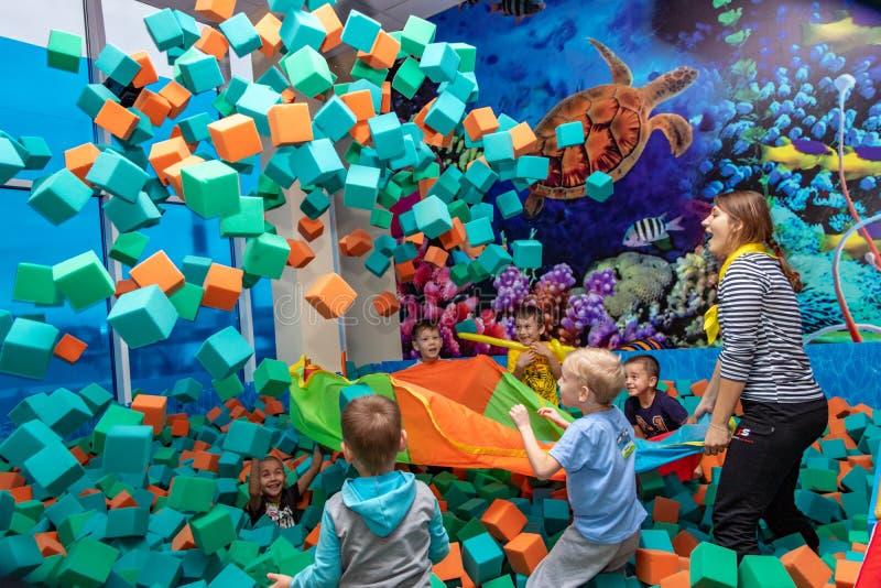 De kinderen spelen met de animator in het vermaakcentrum De kinderen spelen in de pool met zachte kubussen Cheboksary, Rusland, 1 stock afbeeldingen