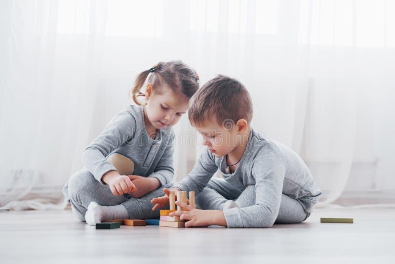 De kinderen spelen met een stuk speelgoed ontwerper op de vloer van de kinderen` s ruimte Twee jonge geitjes die met kleurrijke b stock afbeelding