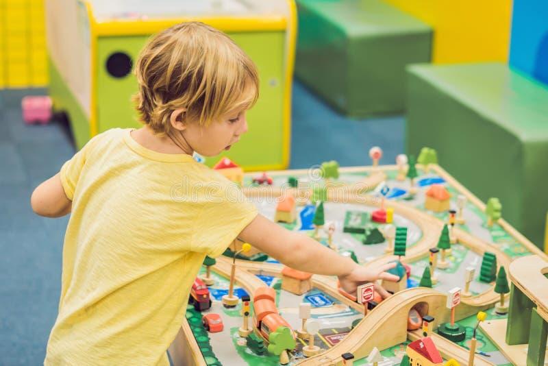 De kinderen spelen met houten stuk speelgoed, bouwen stuk speelgoed spoorweg thuis of opvang Het spel van de peuterjongen met kra stock foto's