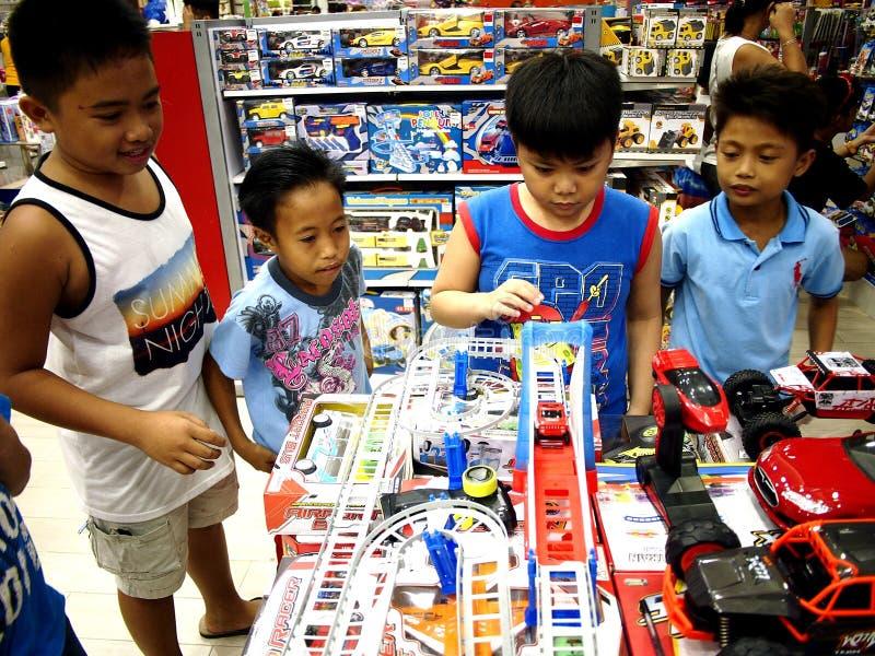 De kinderen spelen met speelgoed in een stuk speelgoed opslag in SM-Stadswandelgalerij in Taytay-Stad, Filippijnen stock afbeeldingen