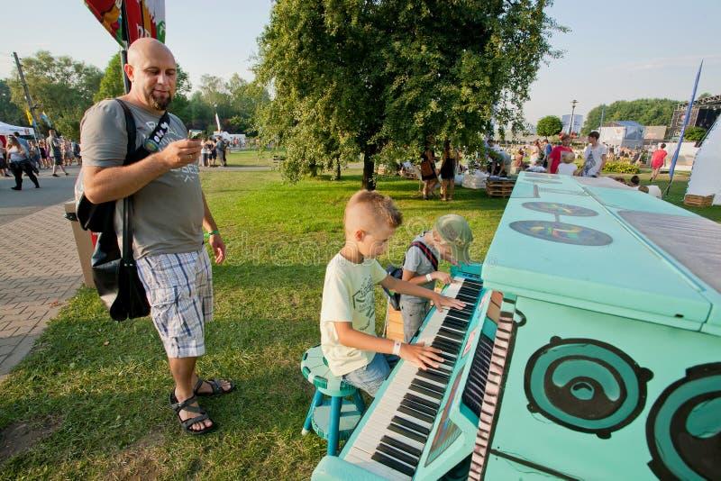 De kinderen spelen piano met vader op een groene speelplaats royalty-vrije stock foto's