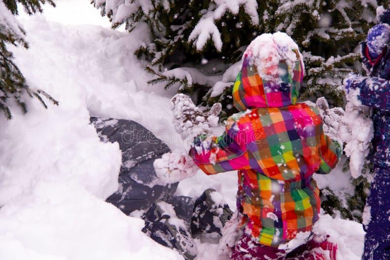 De kinderen spelen in de sneeuw na zware sneeuw, bergen van sneeuw stock foto