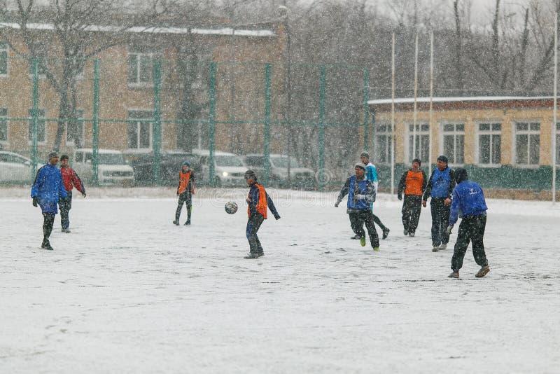 De kinderen spelen voetbal in het sneeuwstadion in de winter in de straat stock foto's