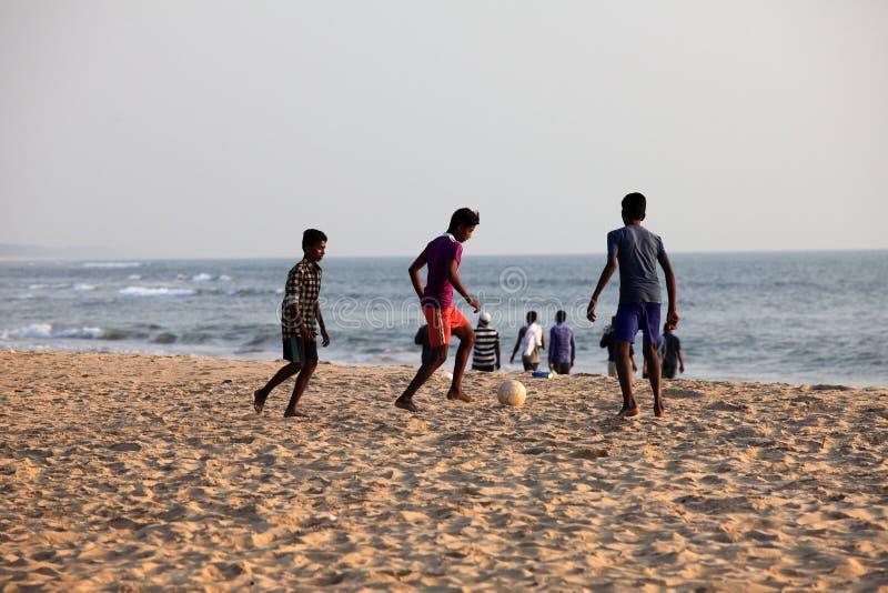 De kinderen spelen voetbal in het zandige strand royalty-vrije stock foto's