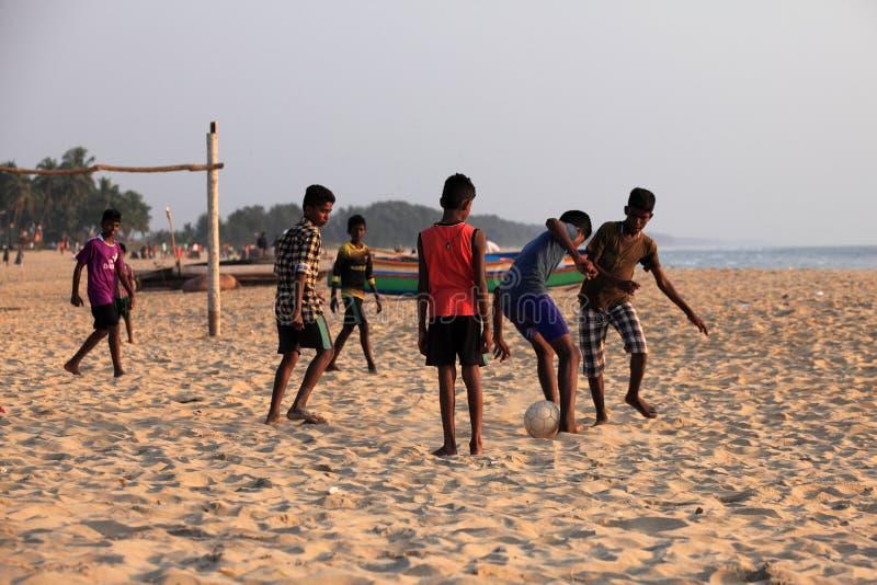 De kinderen spelen voetbal in het zandige strand stock afbeeldingen