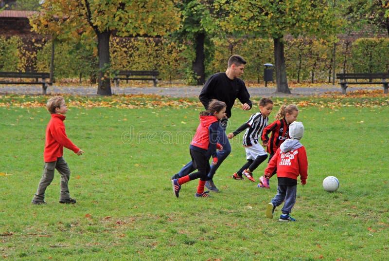 De kinderen spelen voetbal in stadspark stock fotografie