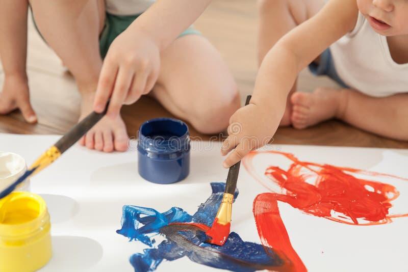 De kinderen trekken heldere kleuren op papier, zittend op de vloer stock afbeelding
