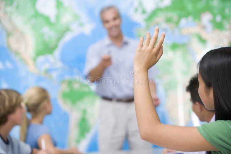 De kinderen van de school en hun leraar in een klasse stock afbeeldingen