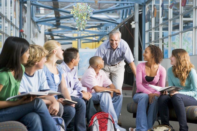 De kinderen van de school en hun leraar in een klasse stock foto's