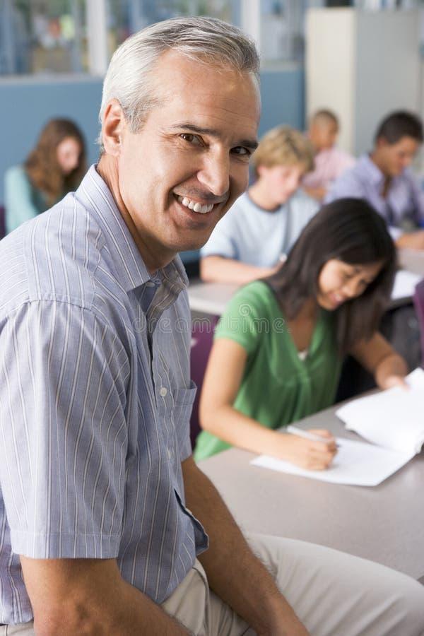 De kinderen van de school en hun leraar in klasse stock foto