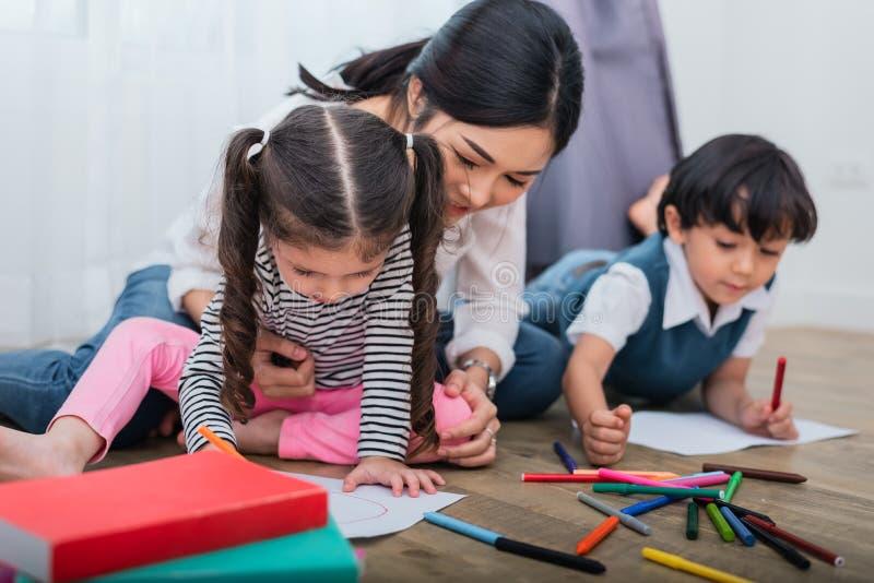De kinderen van het moederonderwijs in tekeningsklasse Dochter en zoons het schilderen met kleurrijke kleurpotloodkleur in huis L royalty-vrije stock afbeeldingen