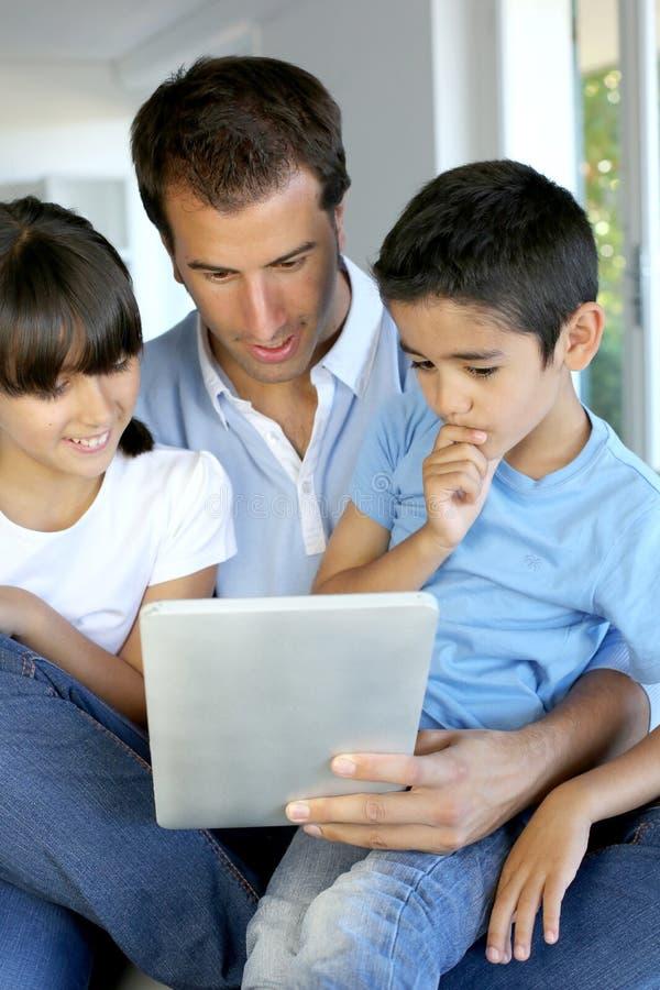 De kinderen van het vaderonderwijs hoe te om tablet te gebruiken royalty-vrije stock foto's