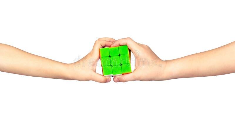 De kinderen verzamelen rubik kubus Rubikkubus in handen stock afbeelding