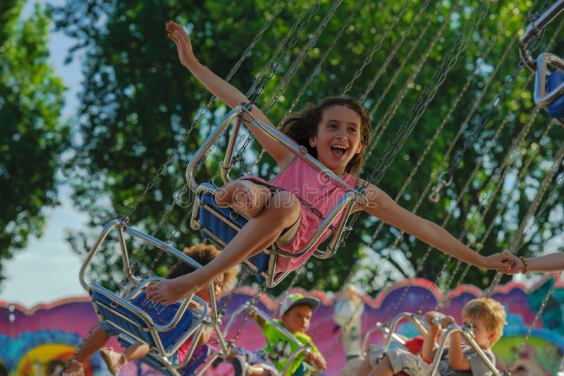 De kinderen zijn gelukkig in de carrousel royalty-vrije stock fotografie