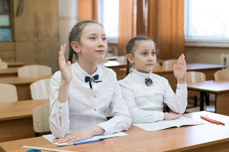 De kinderen zitten in school, heft men zijn hand op royalty-vrije stock foto