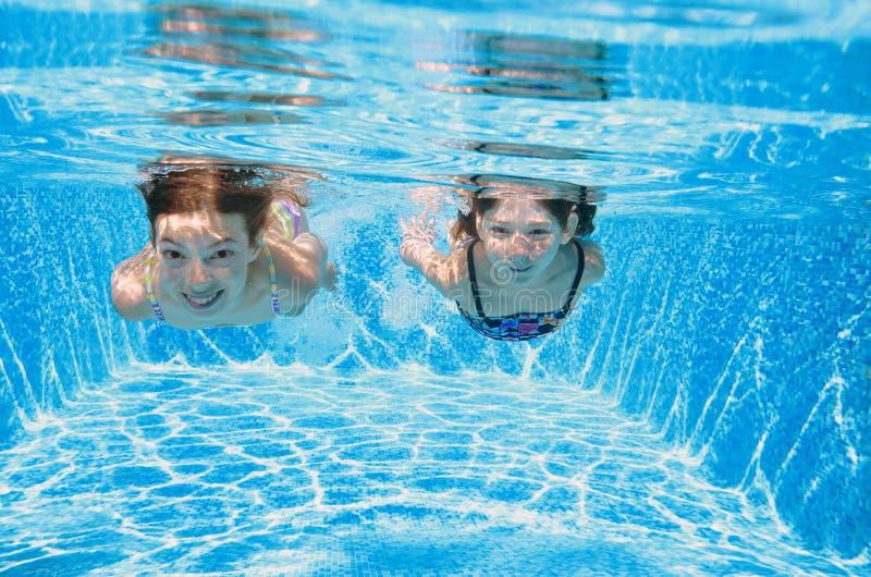 De kinderen zwemmen in pool onderwater, hebben de gelukkige actieve meisjes pret in water, jonge geitjesfitness en sport op famil stock afbeeldingen