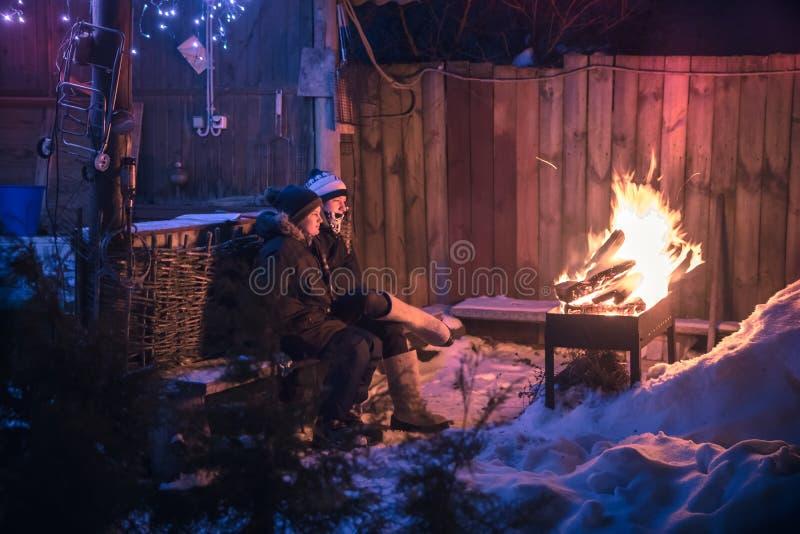 De de kinderenjongens van de de winterscène worden warm bij brand in nacht sneeuwplatteland stock afbeeldingen