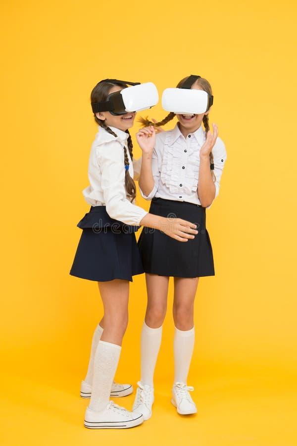 De kinderenschoolmeisjes dragen draadloze VR-glazen Het onderzoeken van vergrote werkelijkheid De ervaringen delen en beheren pro stock fotografie