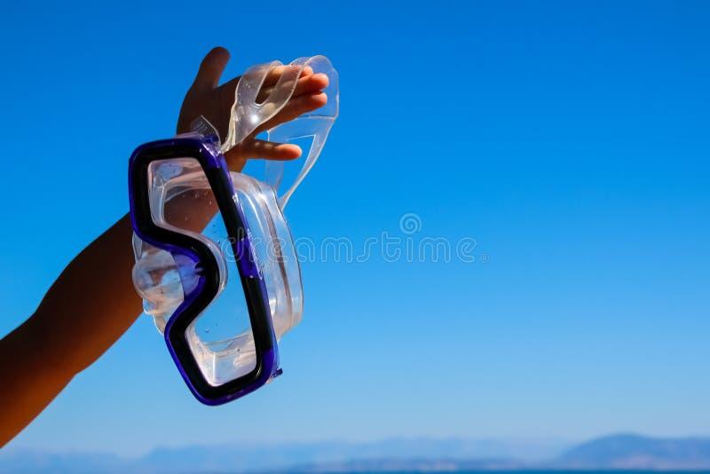 De kindhand houdt een masker voor het snorkelen op water en blauwe hemelachtergrond Het concept van de de activiteitenrecreatie v royalty-vrije stock afbeelding